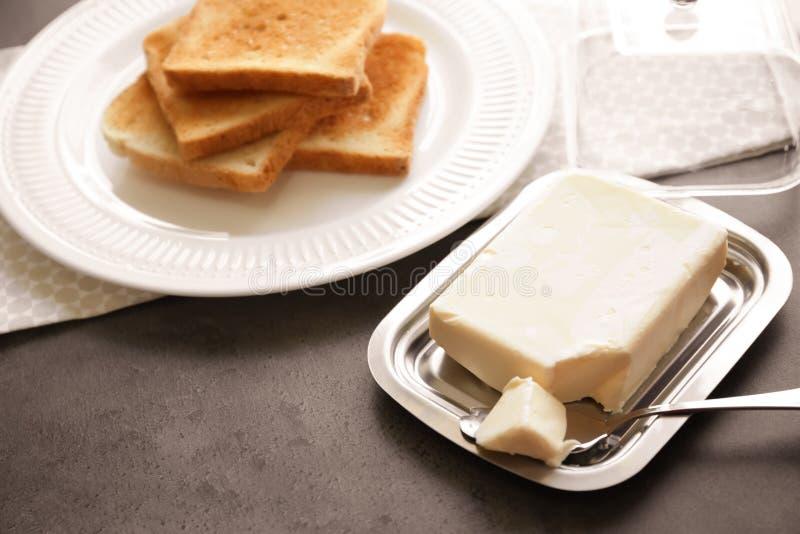 Stuk van heerlijk boter en mes in schotel stock fotografie