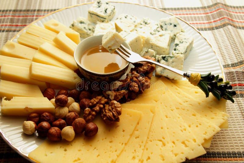 Stuk van kaas op een vork, onderdompeling in honing stock afbeeldingen