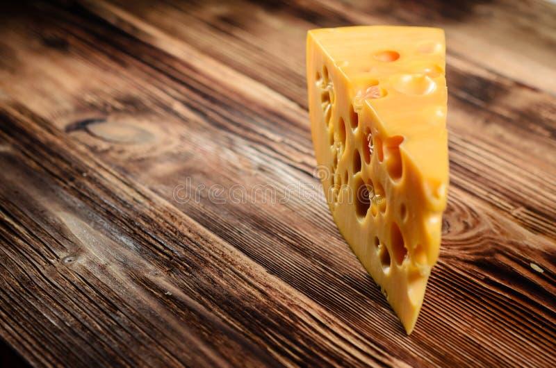 Stuk van kaas op houten lijst royalty-vrije stock afbeeldingen