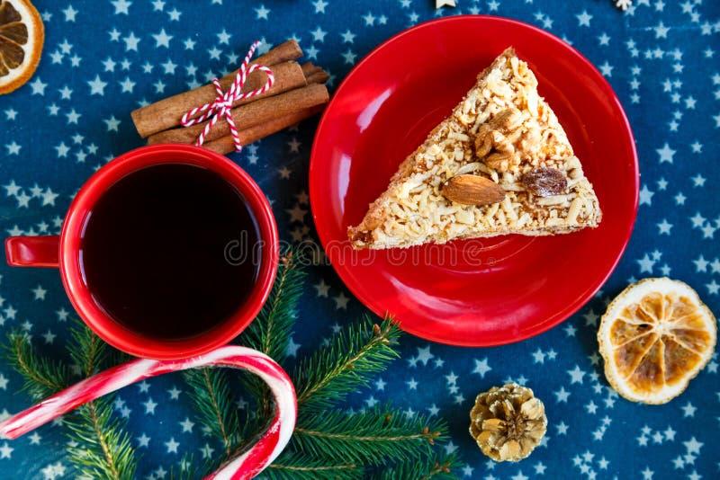Stuk van met de hand gemaakte abrikozenpastei op rode plaat en rode kop met thee of koffie met spar, pijnbomen, kaneel op blauwe  royalty-vrije stock foto
