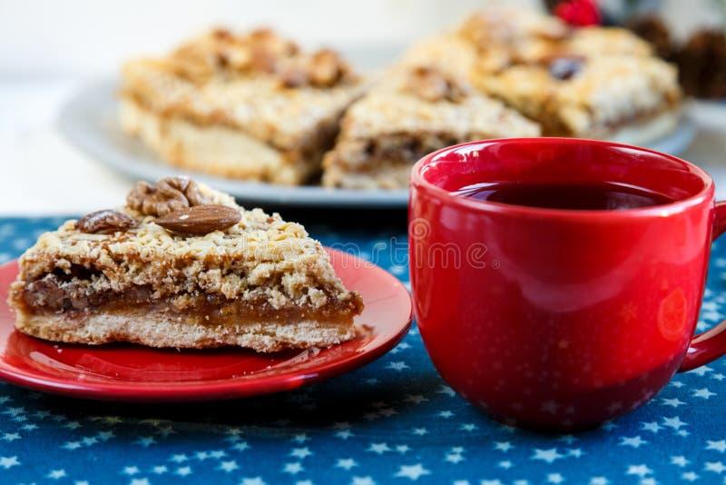 Stuk van met de hand gemaakte abrikozenpastei op rode plaat en rode kop met thee of koffie met spar, pijnbomen, kaneel op blauwe  stock fotografie