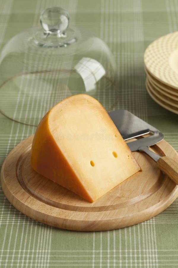 Stuk van Nederlandse Goudse kaas op een houten raad royalty-vrije stock foto's