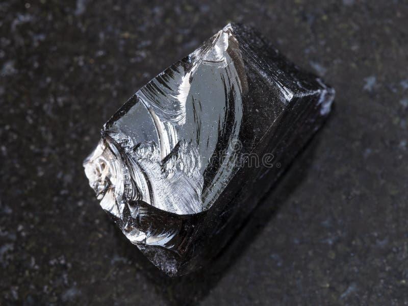 stuk van ruwe Obsidian (vulkanisch glas) op dark stock foto