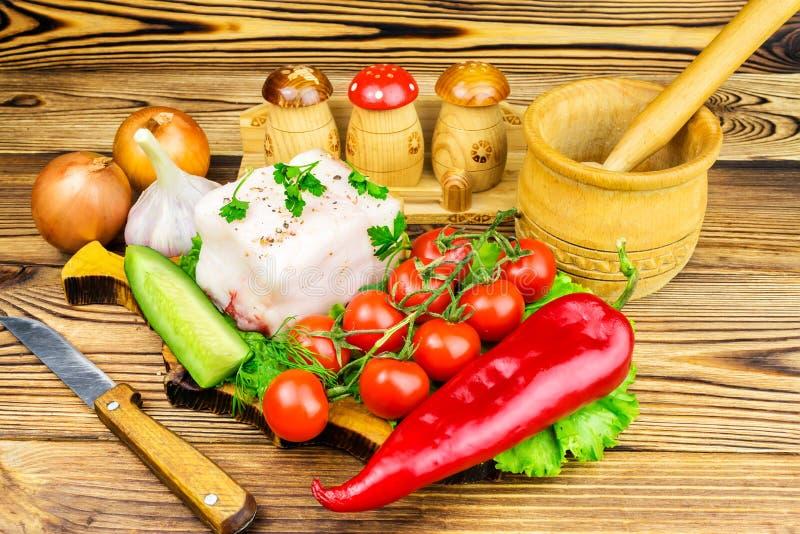 Stuk van verse varkensvleesreuzel, vers product, greens, groenten op de houten raad en mes op lijst royalty-vrije stock fotografie