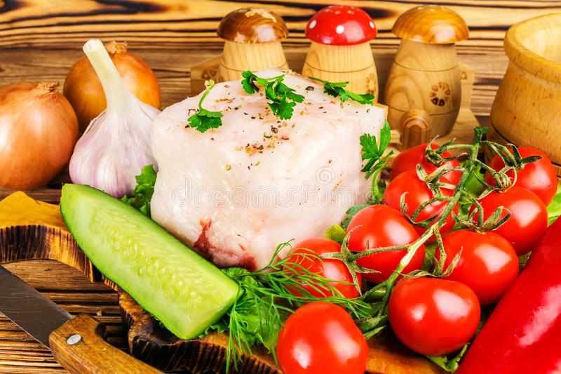 Stuk van verse varkensvleesreuzel, vers product, greens, groenten op de houten raad en mes op lijst, close-up royalty-vrije stock afbeelding