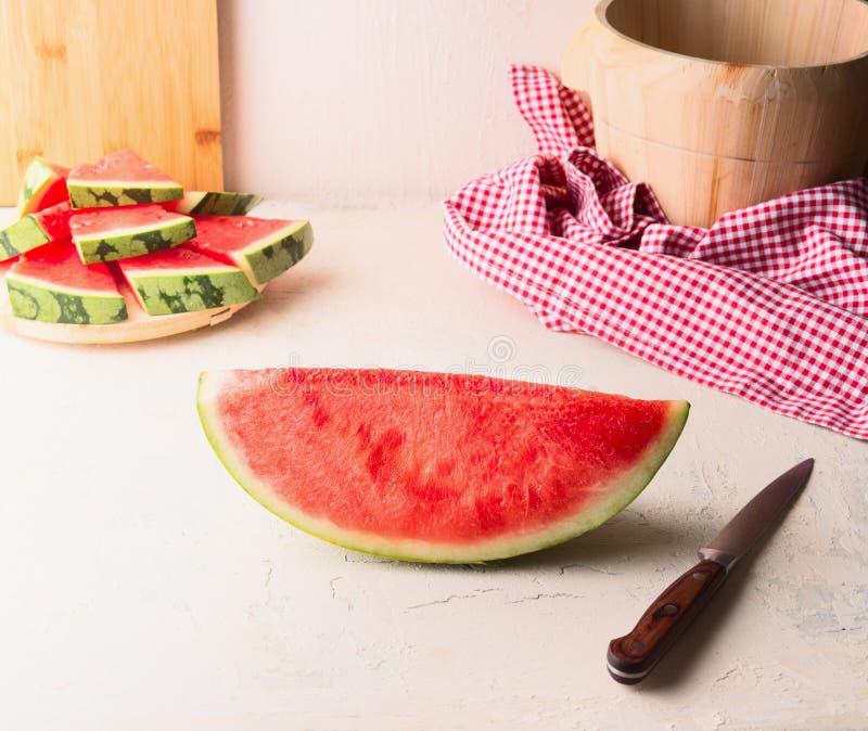 Stuk van watermeloen op witte lijst bij muurachtergrond met mes Sappig verfrissend de zomervoedsel De ruimte van het exemplaar stock foto