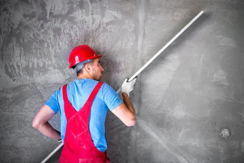 Stukadoor aan het werk aangaande bouwwerf, nivellerende muren en het controleren van kwaliteit Fabrieksarbeider op bouwwerf royalty-vrije stock foto's