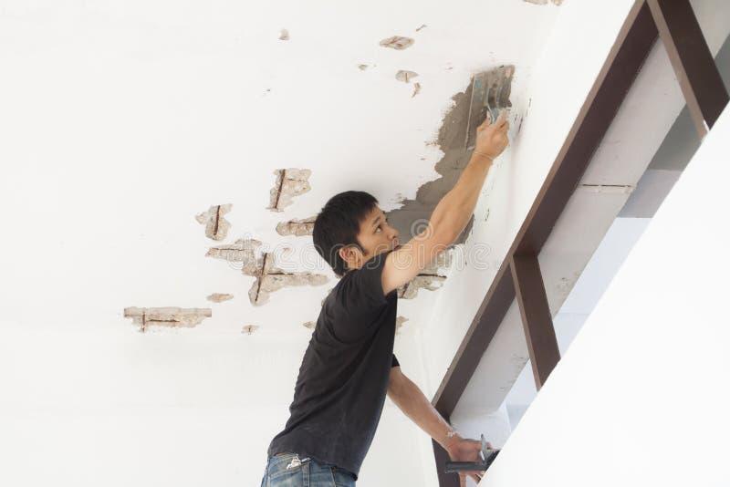 Stukadoor bij de decoratie van de plafondvernieuwing stock foto