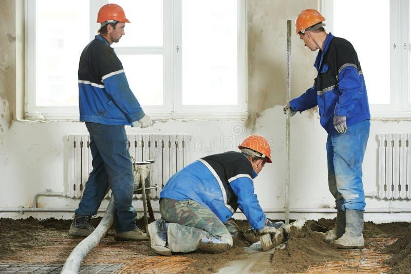 Stukadoren concrete arbeider aan het vloerwerk royalty-vrije stock fotografie
