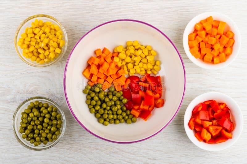 Stukken peper, wortel, groene erwten, graan in ceramische kom en glaskommen met ingrediënten op lijst Hoogste mening stock afbeeldingen