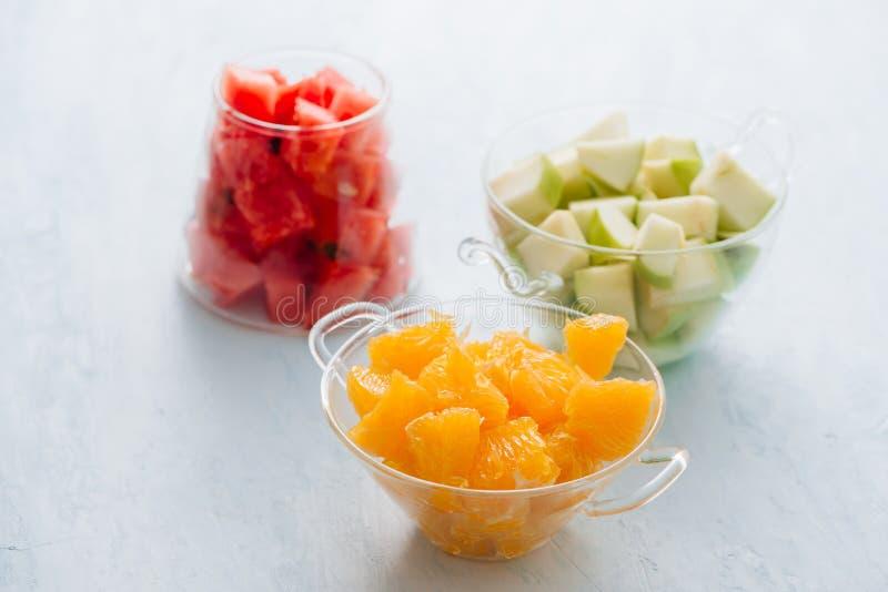 Stukken tropische vruchten in een glas Gesneden sinaasappel, slic appel, stock afbeelding