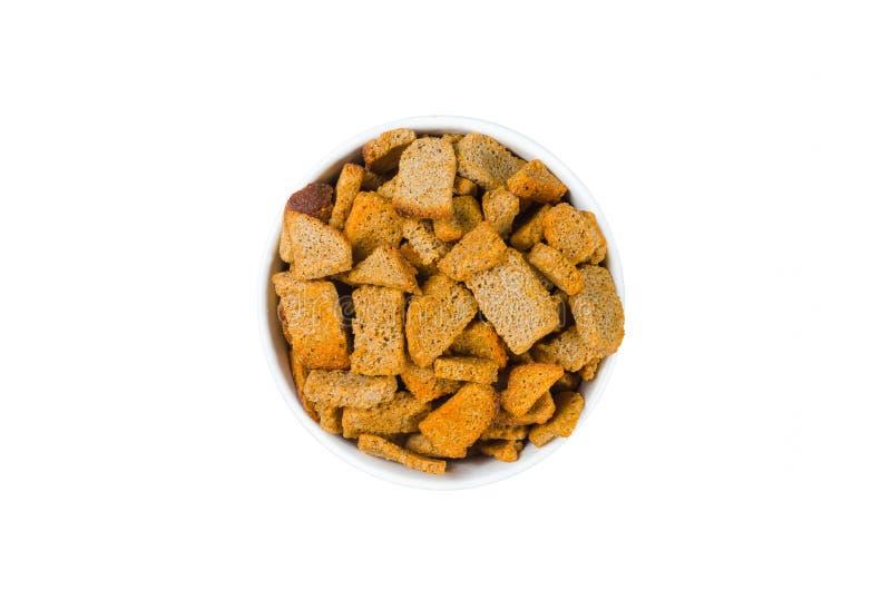 Stukken van bruin droog brood in een ronde die plaat op wit wordt geïsoleerd stock fotografie