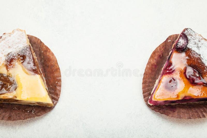 Stukken van cake met een gelaagde bessenlaag op een witte achtergrond stock afbeelding