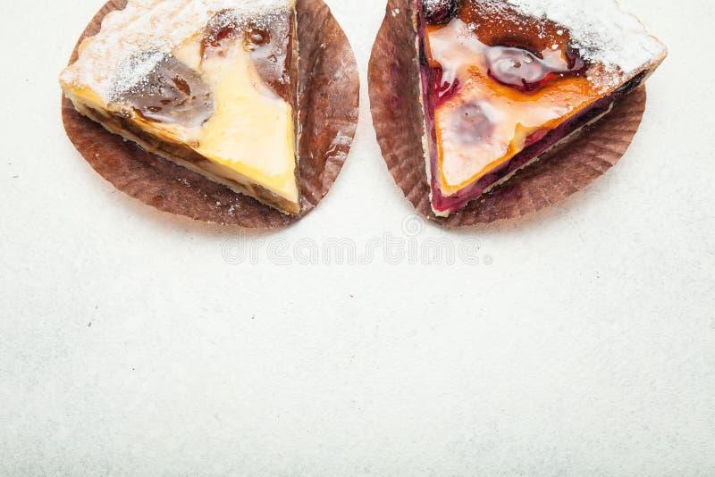 Stukken van cake met een gelaagde laag van de fruitbes op een witte achtergrond Hoogste mening stock fotografie