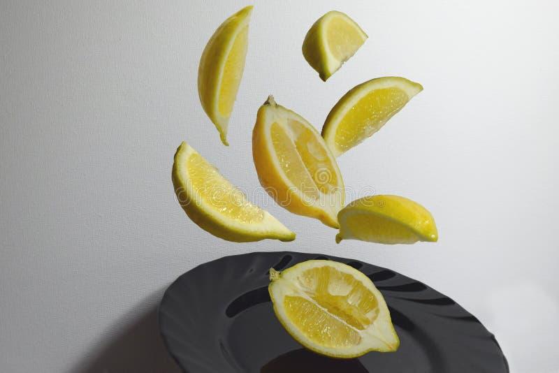 Stukken van citroen die in de lucht op de zwarte plaat vliegen stock afbeeldingen