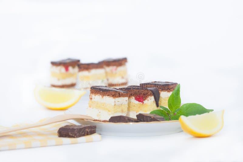 Stukken van citroenbiscuitgebak met chocoladeglans op een plaat stock fotografie