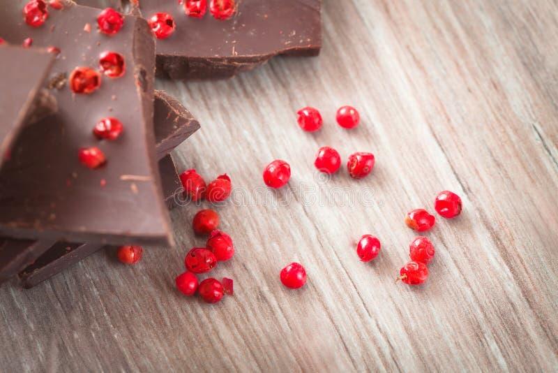 Stukken van donkere chocolade met roze peper stock afbeelding
