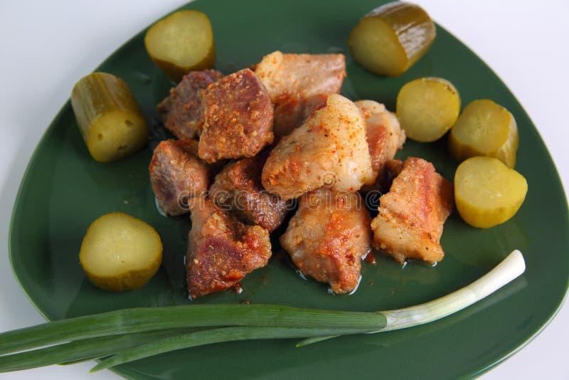 Stukken van gebakken vlees op een groene schotel stock foto