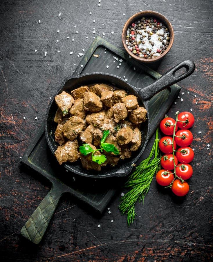 Stukken van gekookte lever in een pan op een scherpe Raad met tomaten, kruiden en kruiden royalty-vrije stock foto's