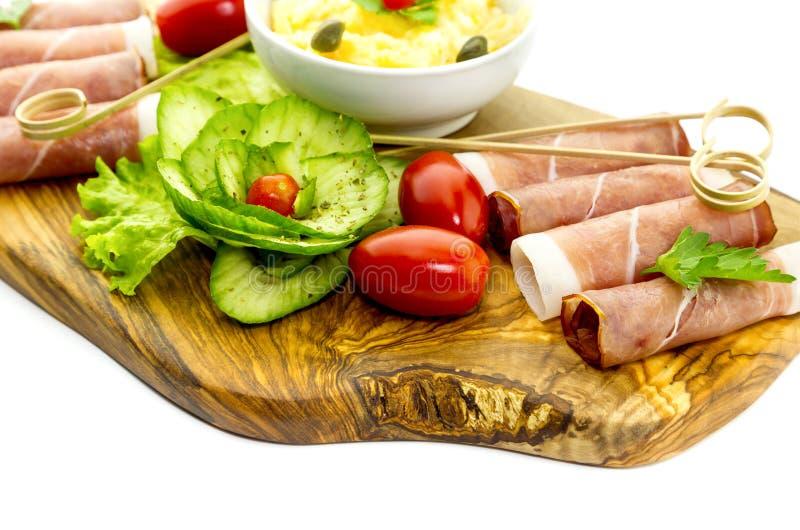 Stukken van Italiaanse prosciutto op een houten scherpe raad stock afbeelding