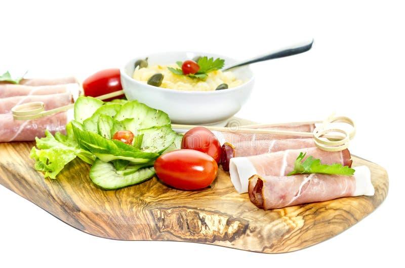 Stukken van Italiaanse prosciutto op een houten scherpe raad stock fotografie