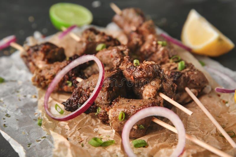 Stukken van kebab op perkament, close-up stock afbeeldingen