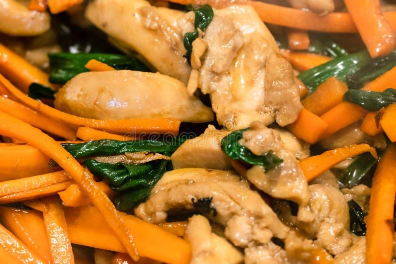 Stukken van kippenvlees het braden met gesneden wortelen royalty-vrije stock fotografie