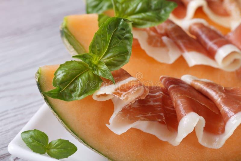 Stukken van meloen met ham en basilicum horizontale macro stock afbeeldingen