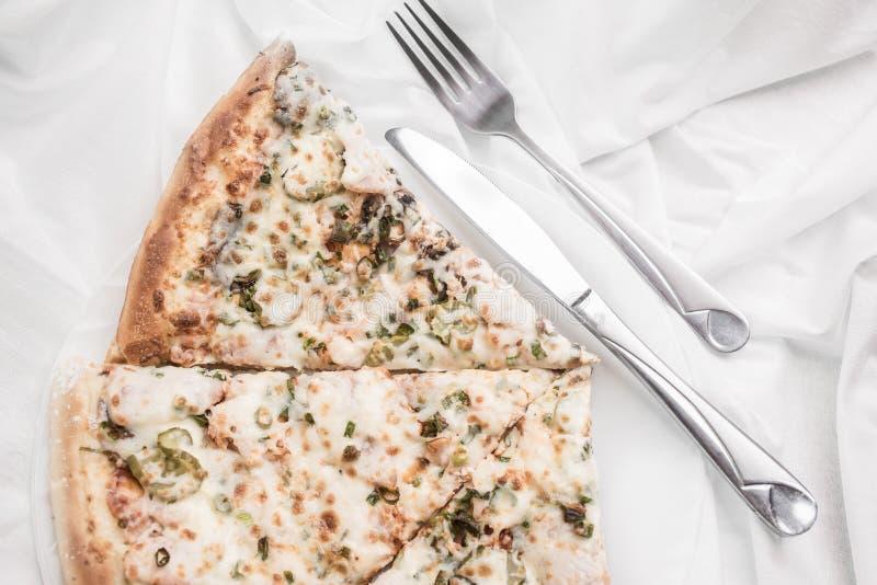 Stukken van pizza op een plaat, een vork en een mes op een wit tafelkleed royalty-vrije stock foto