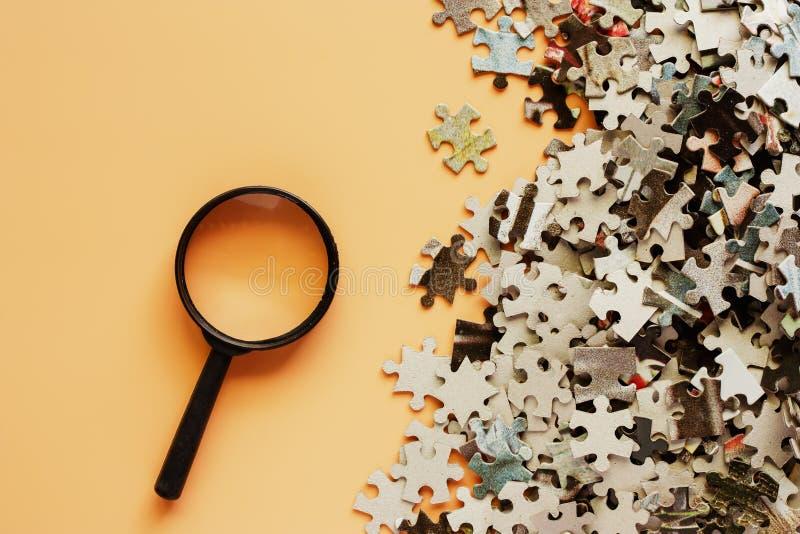 Stukken van puzzel met vergrootglas op beige kleurenbac stock foto's