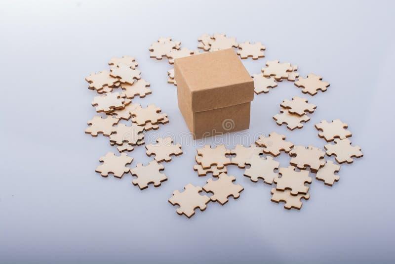 Stukken van puzzel rond doos als concept van de probleemoplossing royalty-vrije stock afbeeldingen