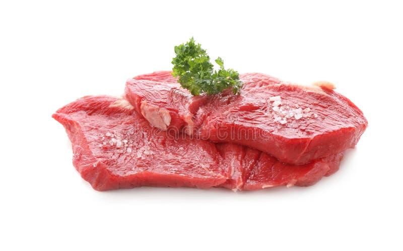 Stukken van ruw vlees met peterselie en zout op witte achtergrond royalty-vrije stock afbeeldingen