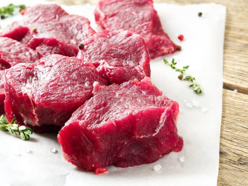 Stukken van ruw vlees Ruw rundvlees met kruiden en thyme op houten ruwe rustieke achtergrond, zijaanzicht, close-up royalty-vrije stock afbeeldingen