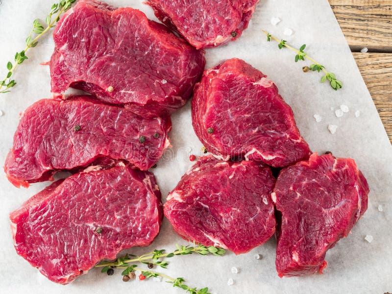 Stukken van ruw vlees Ruw rundvlees met kruiden en thyme op witte parc stock afbeeldingen