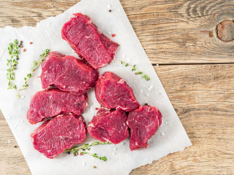 Stukken van ruw vlees Ruw rundvlees met kruiden en thyme op witte parc royalty-vrije stock afbeelding