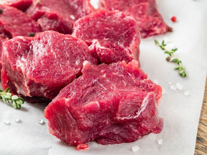 Stukken van ruw vlees Ruw rundvlees met kruiden en thyme op witte parc stock fotografie