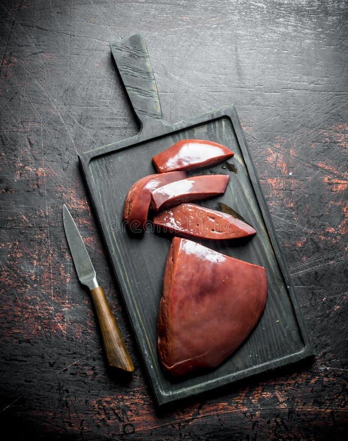 Stukken van ruwe lever met een mes op de scherpe Raad stock afbeeldingen