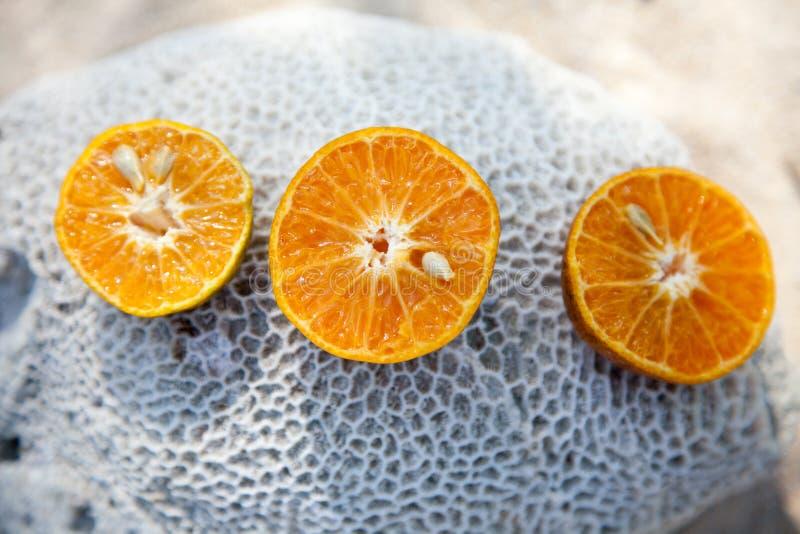 Stukken van sinaasappel op een steen stock foto