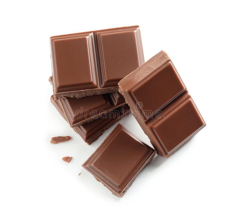 Stukken van smakelijke melkchocola op witte achtergrond stock afbeelding