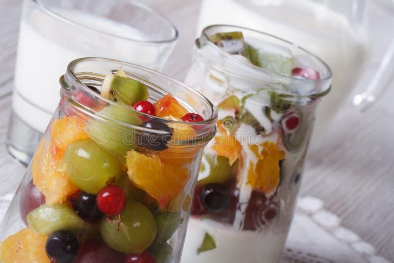 Stukken van vers fruit in een horizontale glaskruik en een yoghurt stock foto's