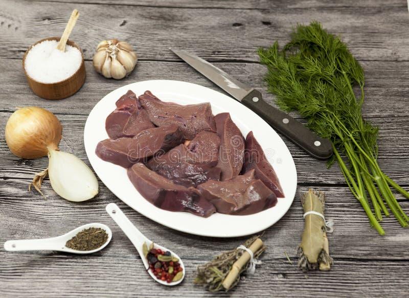 Stukken van verse ruwe rundvleeslever, ui, knoflook, kruiden, dille, peterselie, zout, mes, olijfolie op porseleinplaat op een ho stock afbeelding
