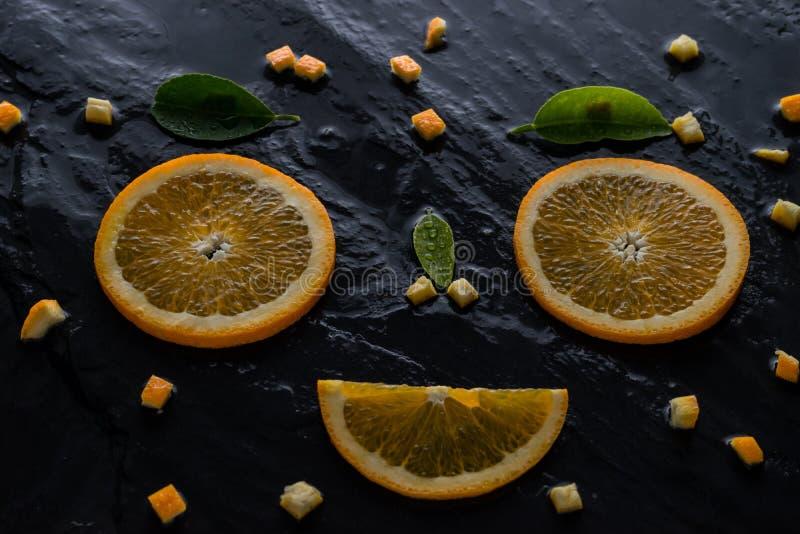Stuksinaasappel en mes op leisteen royalty-vrije stock foto's