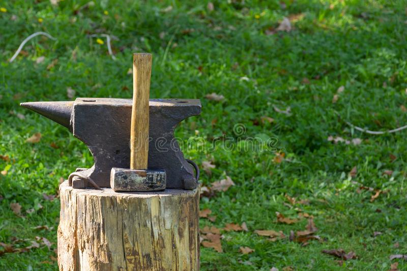 On the stump of a blacksmith`s tools: hammer and anvil. The concept of manual labor, craft. Copy space stock images
