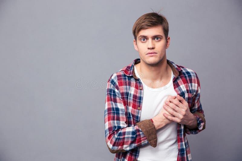 Stunned bedövade mannen i rutig skjorta med handen på bröstkorg royaltyfria foton
