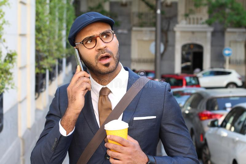 Stunned businessman during phone call outdoors royalty free stock photography