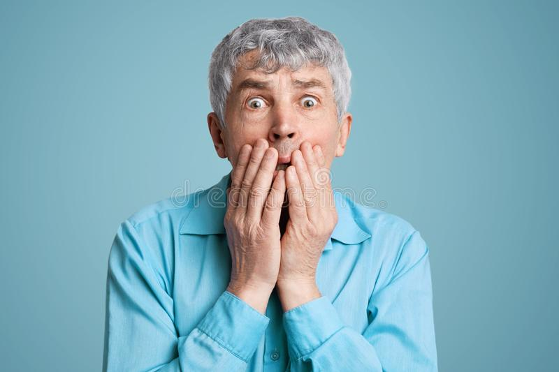 Stunned frightened elderly male model covers mouth with hands, being surprised and scared to hear shocking news, can`t believe in. Disaster, isolated over blue royalty free stock image