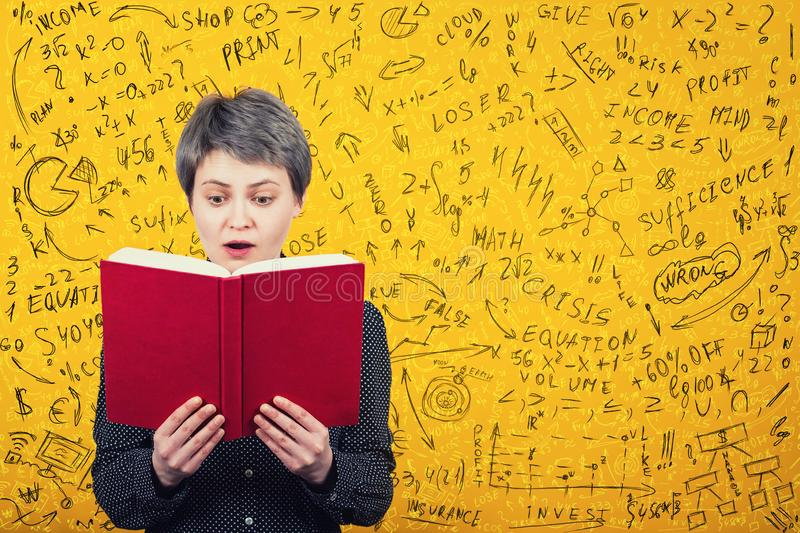 Stunned woman reader looking amazed in a book. Mathematics calculations, economics formula and equations difficult to solve. Ideas royalty free stock photos