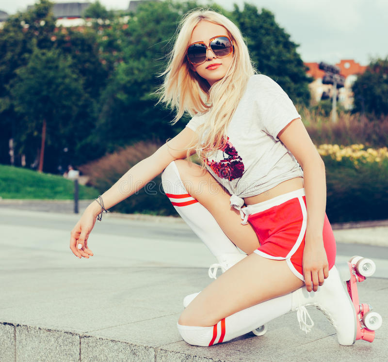 A stunner summer closeup portrait of young happy woman posing in a vintage roller skates, sunglasses, T-shirt, shorts posing stock photography