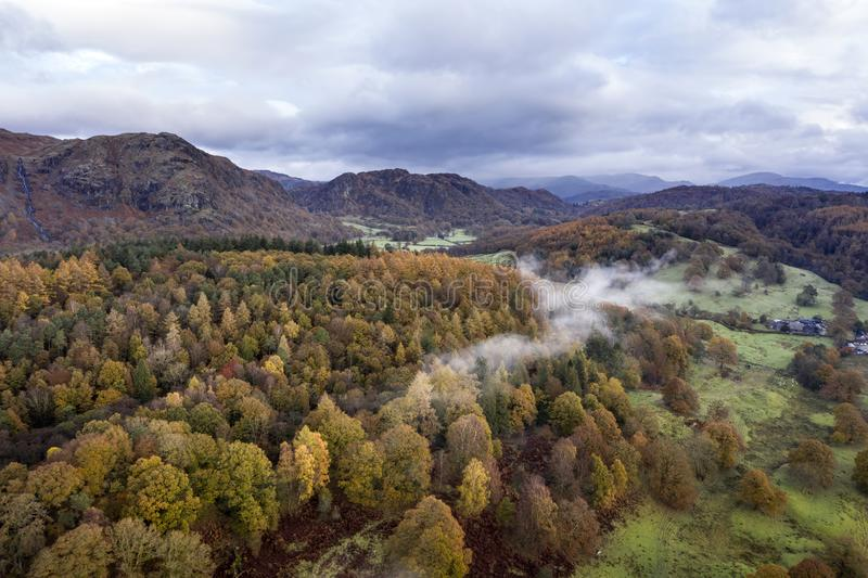 Stunning aerial drone landscape image from in the clouds looking down on hills and valleys on a vibrant Autumn Fall morning stock image