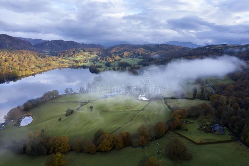 Stunning aerial drone landscape image from in the clouds looking down on hills and valleys on a vibrant Autumn Fall morning royalty free stock photo